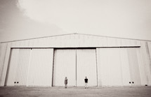 A couple stands in front of an airplane hangar