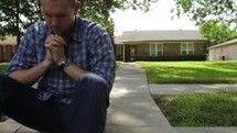 Man sitting on a curb in front of mailbox and house in prayer.