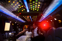 bride and groom kissing at the back of a limo