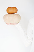 woman holding out stacked pumpkins