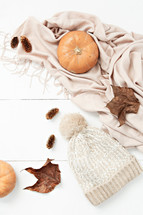 scarf, pumpkin, fall leaves, pine cones, and beanie on a white wood background