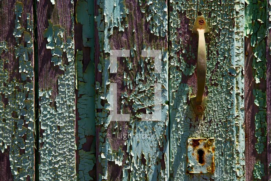 paint pealing off a wood door and brass door pull