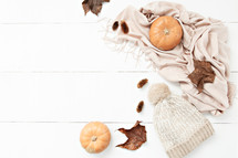 pumpkins, leaves, scarf, and pine cones on a white background