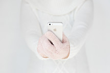 woman in gloves holding a cellphone