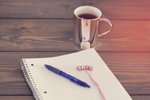 a pen and earbuds on a spiral notebook and a mug of tea