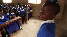 a girl child leading her class in song