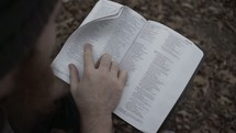 man walking through the forest carrying a Bible looking for a quiet place to read