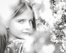 face of a little girl behind spring branches