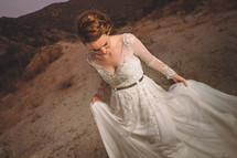 a portrait of a bride holding up the bottom of her wedding dress