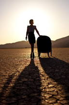 silhouette of a woman standing beside a chair on parched earth