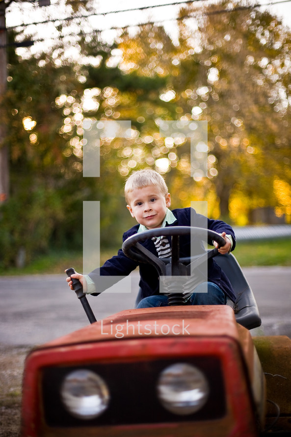 toddler boy riding a lawn mover