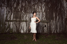 bride standing in front of an old barn covered in dead ivy