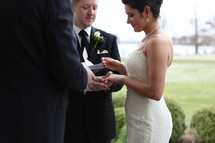 groom putting a ring on his bride finger