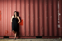 woman in a black dress standing in front of a warehouse