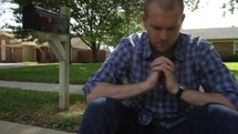 Man sitting on a curb in front of a mailbox and house, praying.