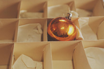 One lonely Christmas ornament in it's box.