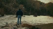 man walking along a riverbank
