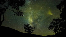 Timelapse of evening stars and cloud movements at night beyond the silhouette of trees and hills.