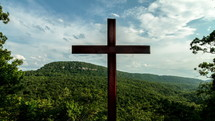 Timelapse of cloud movement over a cross on a hill.
