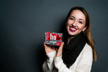 a young woman holding a Christmas gift