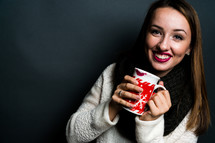 a young woman holding a mug of hot chocolate