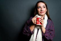 a young woman holding a mug