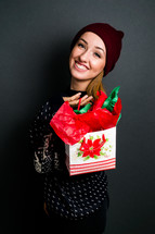 a young woman holding a Christmas gift bag