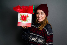 a teen girl in a sweater holding a Christmas gift