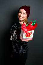 a teen girl holding a Christmas gift