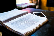an open Bible and cellphone on a table