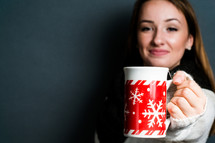 a young woman holding a mug of hot cocoa