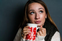 a young woman holding a winter mug