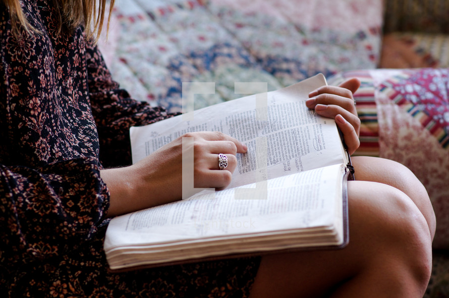 teen girl reading a Bible on a couch