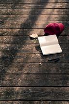 a ball cap, open journal, and pen on a wood deck
