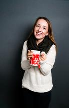 a teen girl holding a winter mug with tea