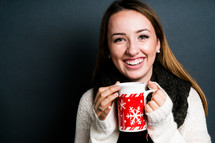 a smiling young woman holding a mug