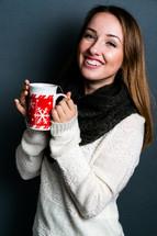 a teen girl holding a mug of hot cocoa