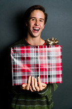 a smiling teen boy with braces holding a Christmas gift
