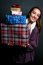 teen girl holding a stack of wrapped Christmas gifts
