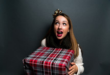 a teen girl holding a wrapped Christmas gift