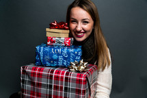 a teen girl holding a stack of Christmas gifts