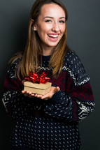 a smiling young woman holding a Christmas gift