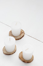candles on wood slices on a white background