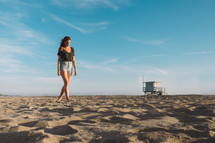 woman walking bare foot on a beach and a distant lifeguard stand