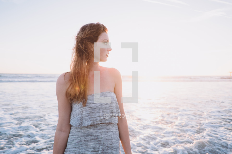 young woman standing on a beach looking to her side