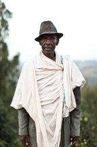 man wearing a hat and blanket