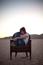 woman sitting on a chair in the parched earth of a desert