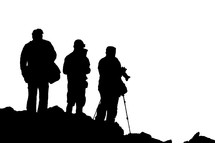 silhouettes of tourists standing in front of a volcano with cameras