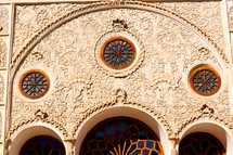 round stain glass windows on a building in Iran
