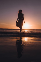 young woman walking into the ocean at sunset